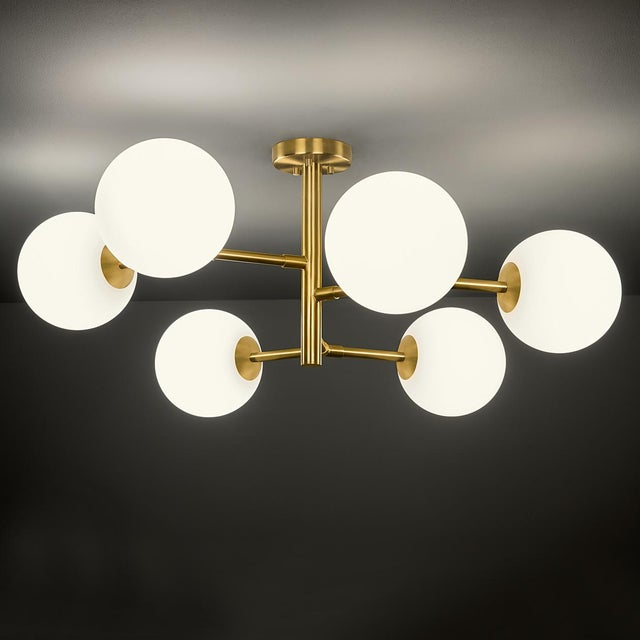 Brushed brass constellation light consisting of 6 arms with opal globes. The glass globes have a threaded insert to screw...