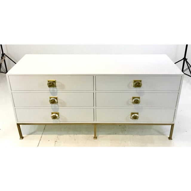 Stylish contemporary white lacquer six drawer dresser, brass metal base and brass and lucite hardware, showroom floor sample