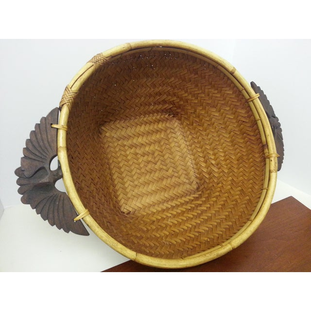 Asian in origin, this woven, rattan basket with carved wooden handles in the shape of eagles, would make a perfect...