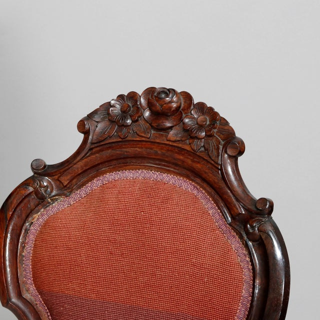 An antique Victorian parlor chair offers walnut frame with shield form back having cared floral crest with flanking scroll...