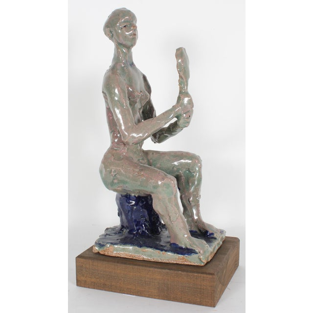 A clay sculpture of a nude female figure sitting up straight with a mirror in hand. Made in the 20th - early 21st century...