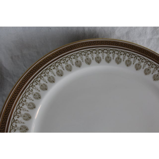 Ten Cauldon lunch plates, made in England, marked 5th Avenue, New York City. White porcelain with golden gilt Greek key...