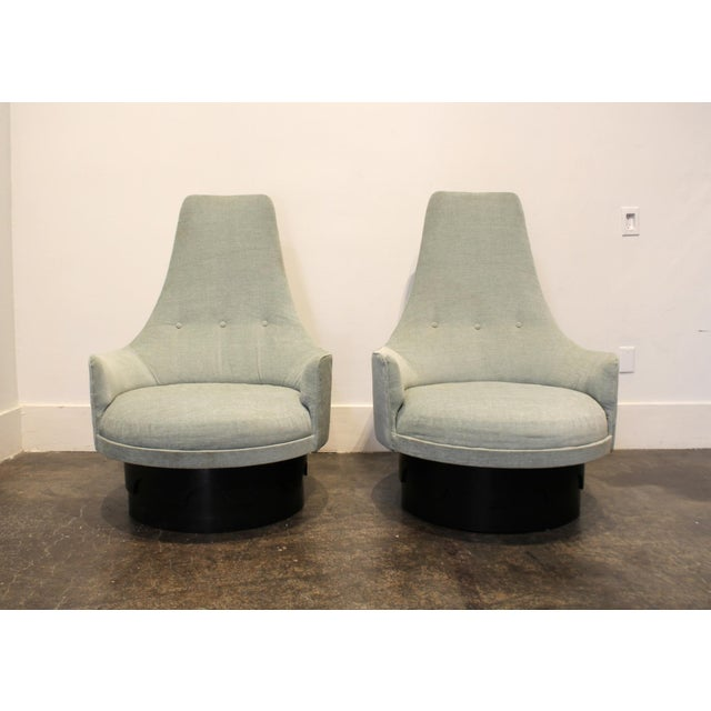 Lovely pair of high-back swivel lounge chairs designed by Adrian Pearsall. Light blue upholstery on top of mahogany...