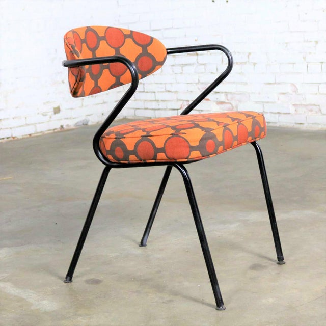 Handsome mid-century modern armchair made of bent steel tube painted black and newly upholstered in an orange contemporary...