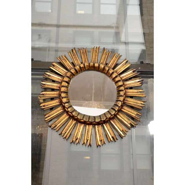 A giltwood sunburst mirror from France with molded center, mid-20th century.