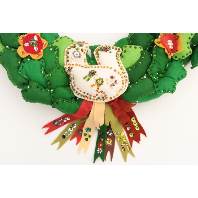 """This vintage 20"""" felt wreath is pieced together on a foam form with pearl stick pins. Each holly leaf is embellished with..."""