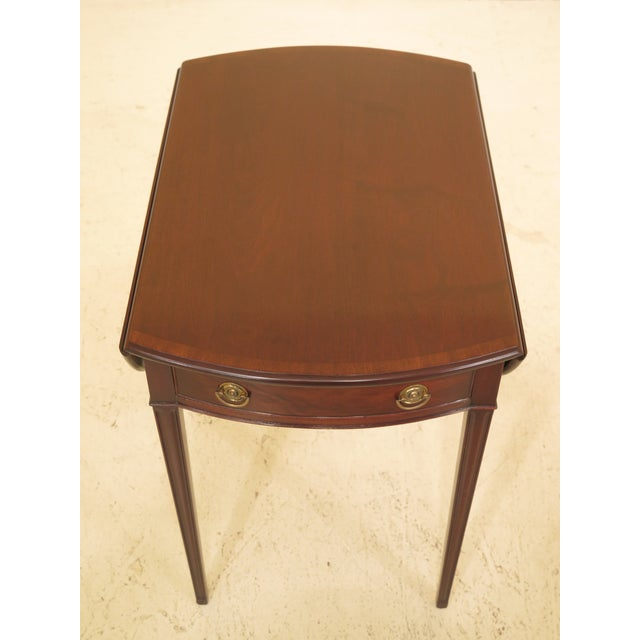Kittinger vintage mahogany drop leaf pembroke table. Features dovetailed drawer construction and solid brass hardware....