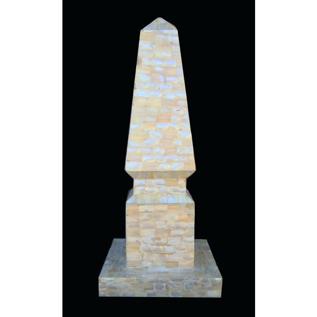Rainbows appear and disappear as the light crosses the surface of this shell overlaid obelisk combining feminine essence...