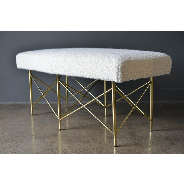 Ivory Bouclé and brass X-base ottoman or bench, circa 1970. Professionally recovered in beautiful soft ivory or cream wool...