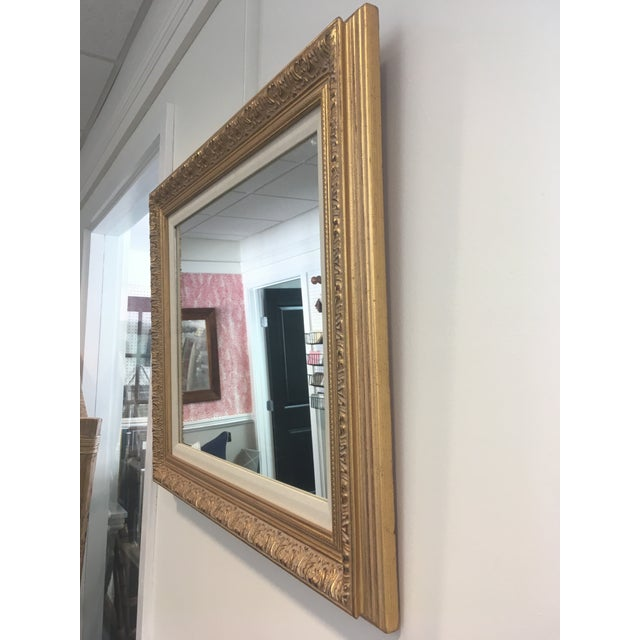 20th Century wood frame with gilded leafing Design. The mirror features a beige fabric inner frame. Perfect for any...