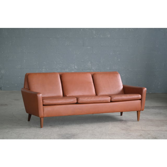 Classic Danish London-Style Mid-Century sofa in cognac colored leather. A nice variation of the style made famous by Borge...