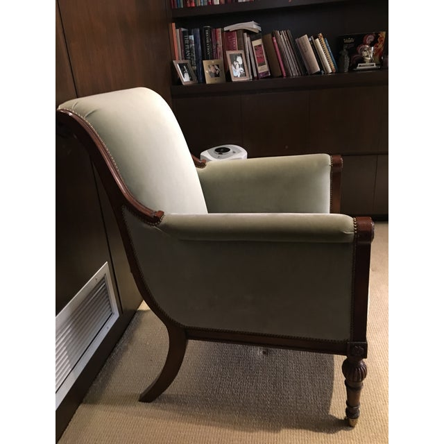 Nancy Corzine Chair. Walnut and Velvet Green with nail heads. Has wheels at the bottom.