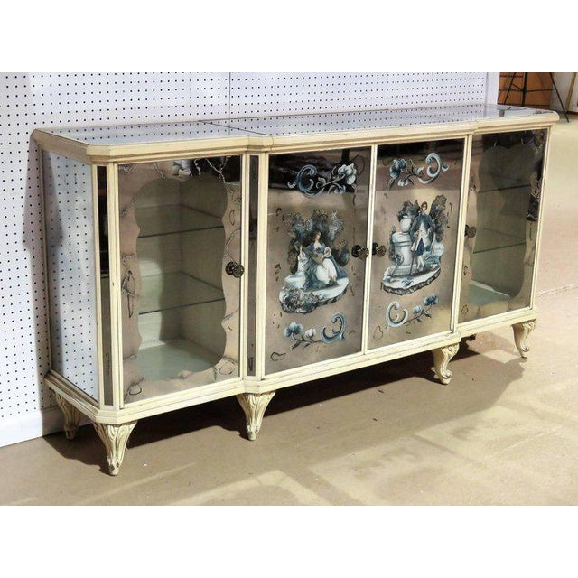 Eglomised mirrored frame with courting scene on doors. Glass shelves. Mirrored bar interior.