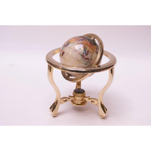 Visually stunning, petite desk globe composed of gemstone inlay and crushed Mother-of-Pearl. Supported by a brass, tripod...