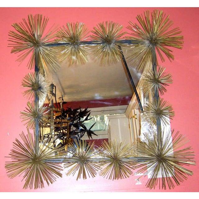 """A black steel frame is embellished with gold tone metal """"pom-poms""""."""