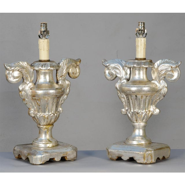 Pair of lamps, of carved silver giltwood, each a porta palma base; a fluted urn with large scrolling handles, on leaf-...