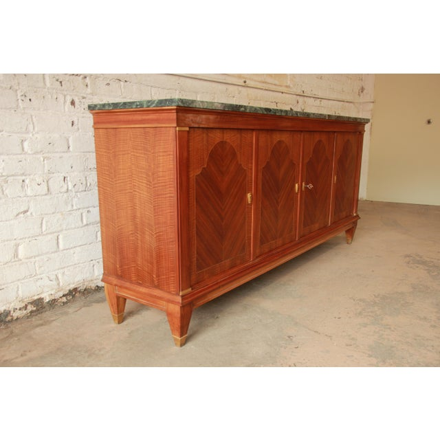 Offering a gorgeous monumental French marble top sideboard or buffet. The sideboard features stunning inlaid mahogany wood...