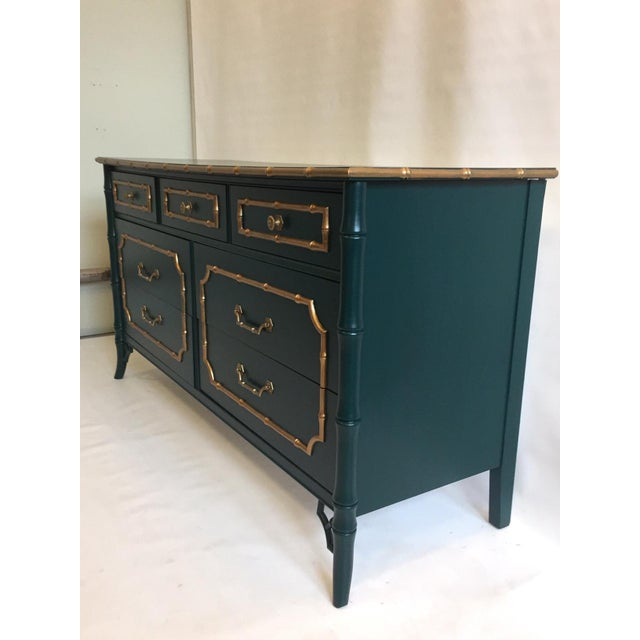 This vintage bamboo dresser with vintage mirror have been meticulously refinished in a dark forest green with metallic...