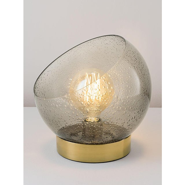 A brushed brass and smoke glass table lamp. The smoke glass globe encloses a warm white LED filament lamp. Prices with and...