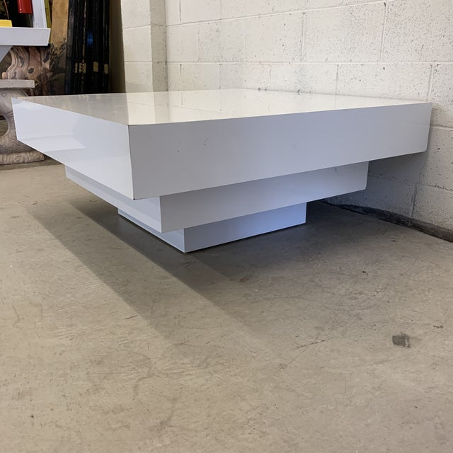 This is a great coffee table. Large and in charge! White glossy laminate over wood. Tiered or stacked cubes gives this a...