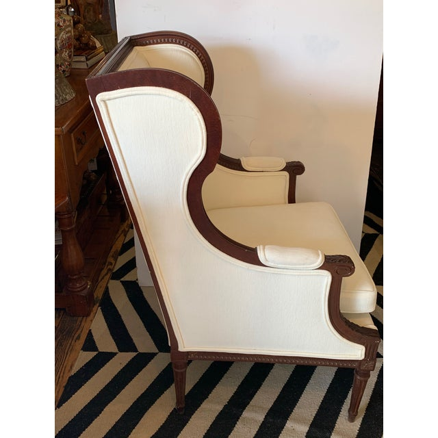 Classic carved walnut wingback chair with lovely shape, off white upholstery with double welting and padded arms with...