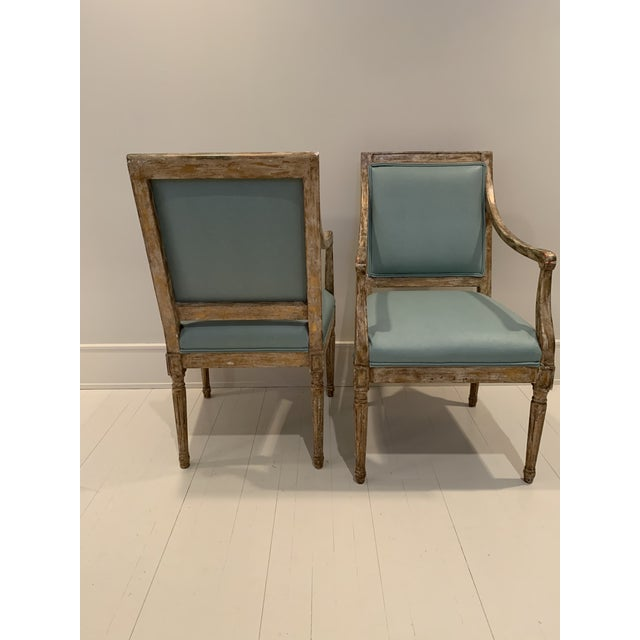 Pair of French salon arm chairs upholstered in Kravet faux leather. Produced by Nancy Corzine with a beautiful gilt patina.