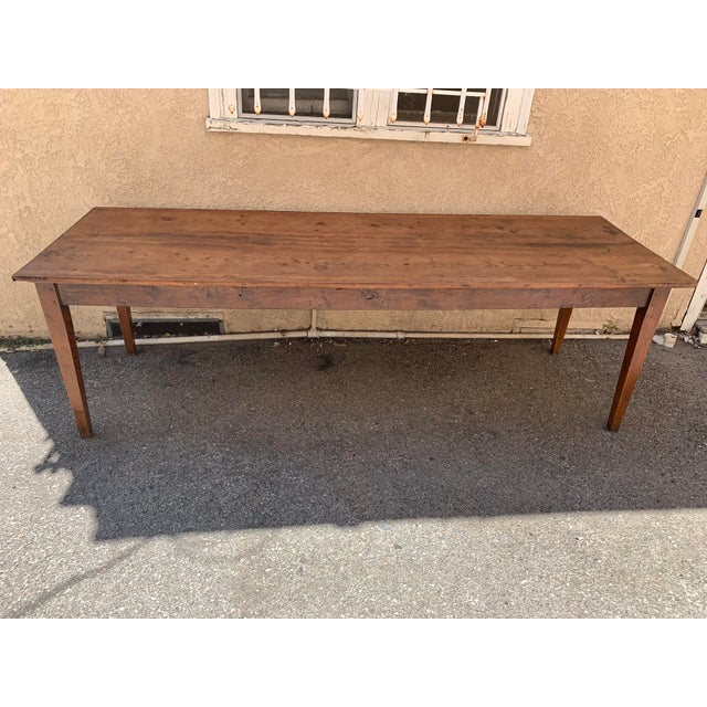 Gorgeous extra long French country farm table with whimsical drawer at one end. Made in the early 19th century.