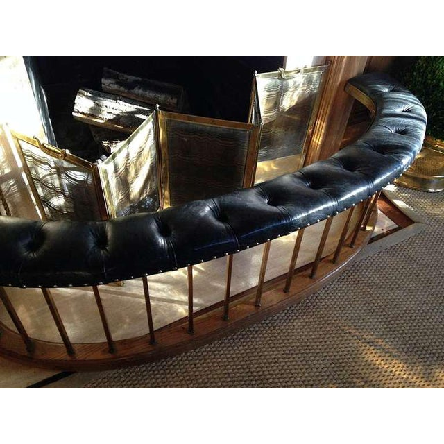 Purchased from a well-known Left Bank Paris dealer, an unusual arc-shaped oak, brass and tufted black leather fireplace...