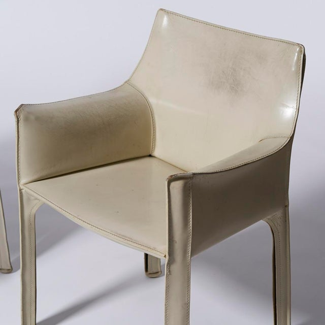 Pair of white leather Cab dining chairs with arms designed by Mario Bellini for Cassina Circa 1970s-80s Chairs have...