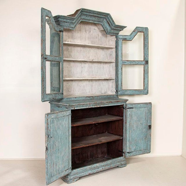 The blue painted finish is captivating in this bookcase or display cupboard from Sweden. Notice the top bonnet or crown...