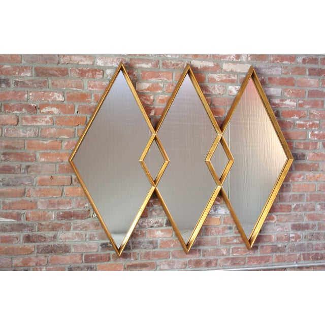Regal Labarge mirror composed of three interlocking diamonds of inset electro copper mirror glass framed by giltwood....