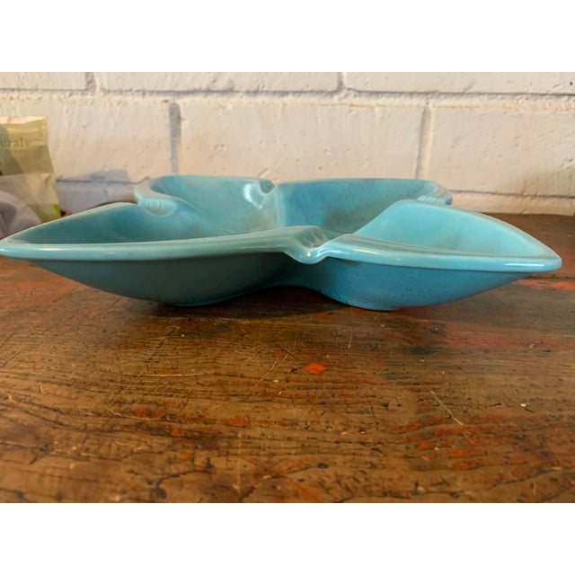 Pretty vintage pottery ashtray in the shape of a star or flower. Turquoise blue with gold accent glaze. Made by Gilner...
