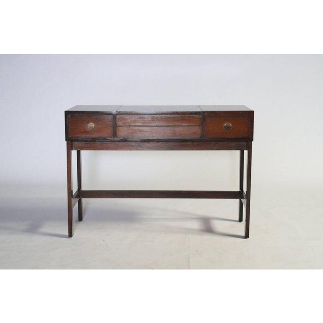 Midcentury rosewood vanity by Drylund, Denmark features a lift-up drawer revealing a make-up mirror and compartments for...