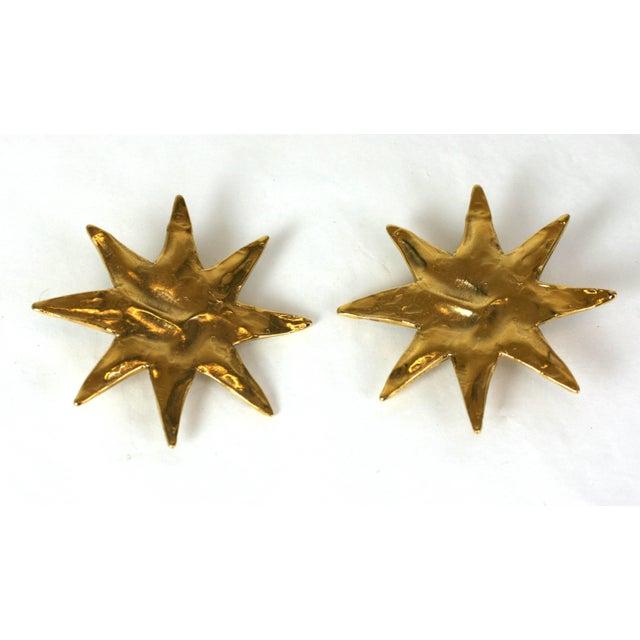 Yves Saint Laurent classic starburst ear clips of gilt hammered metal. Workshop of Maison Goossens. Clip back fitting....