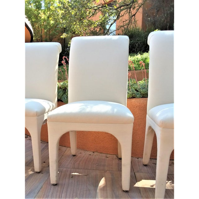 These white cotton duck dining chairs have a rolled top chair back with a pleasing pleated detail. The armless chairs are...