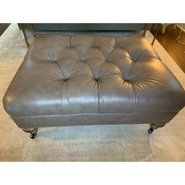 Classic button-upholstered ottoman with rustic casters. Leather in mushroom color. Perfect for feet, trays of coffee,...
