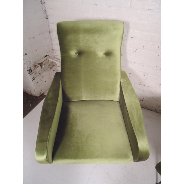 Pair of Marco Zanuso style arm chairs in soft green fabric with black legs and brass caps. (Please confirm item location -...