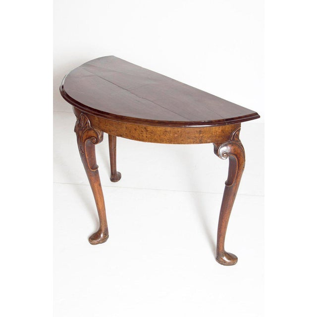 A lovely walnut demi-lune with three cabriole legs resting on pad feet. The two back legs are turned to the rear. The...