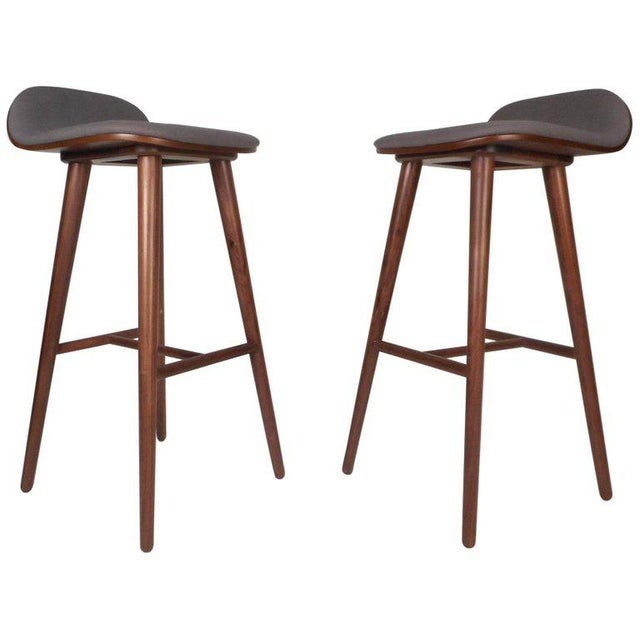 This wonderful pair of Mid-Century Modern style stools feature upholstered seats with raised backs for added support and...