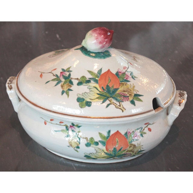 A Chinese Qing Dynasty Famille Rose export tureen with peaches, guava, Buddha's hand and peony blossoms