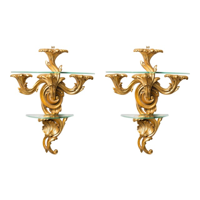 This is an elegant pair of Rococo style wall brackets, the top section with a glass shelf supported by three outscrolled...