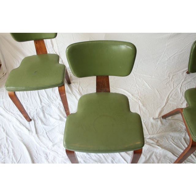 A set of four vintage chairs by Thonet. The chairs feature classic angled frames. They are crafted of bent wood that shows...