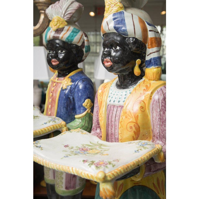 This exquisite pair of early 20th century hand-painted polychrome glazed terracotta blackamoors are dressed with garments...