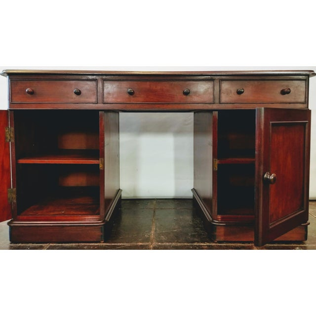 Georgian kneehole desk made in England of West Indian Mahogany wood circa 1760 has a flat top over three frieze drawers...