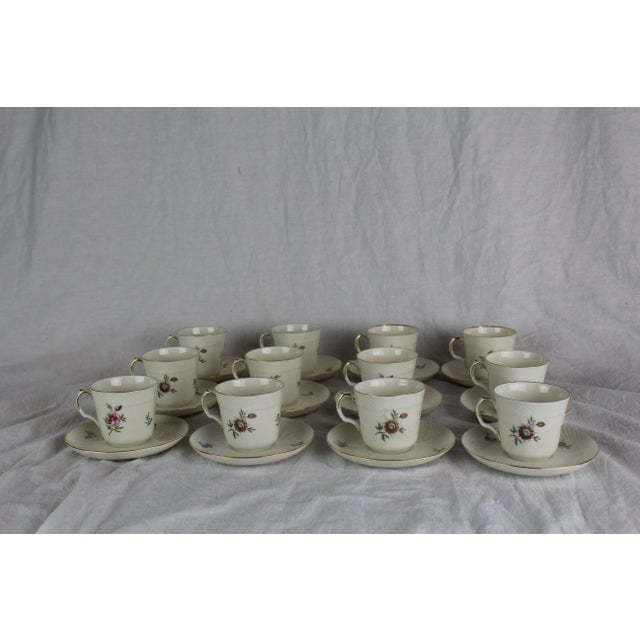 """Twelve Royal Copenhagen demitas cups and saucers. Ribbed molded body with floral design and gilt band. 4.5"""" diameter..."""
