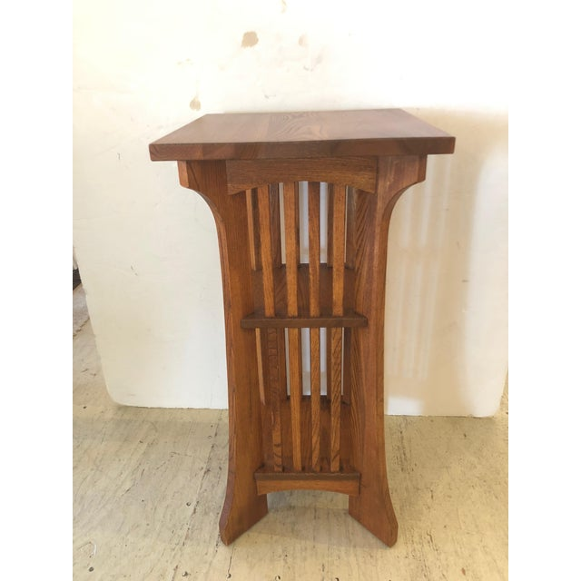 Handsome oak side table in the classic Arts & Crafts style having two shelves, beautiful grain on top, and slightly...
