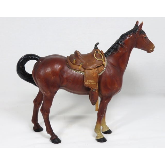 A large size cast iron horse doorstop with a handmade leather saddle. The saddle is marked Chicago Stockyards. Made by the...
