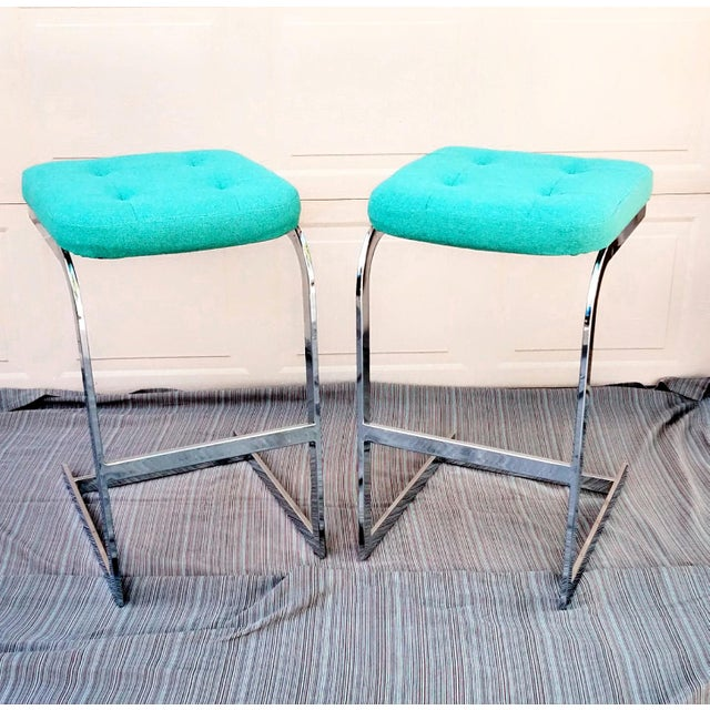 Pair of DIA flat bar, cantalevered chrome stools in the style of Milo Baughman. Original upholstered cushions in teal...