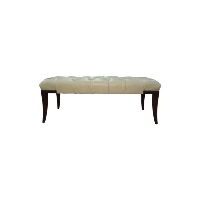 A deeply tufted bench with exposed wood corners outlined with nail head trim. Faring tapered legs. Inspired by a Robert...