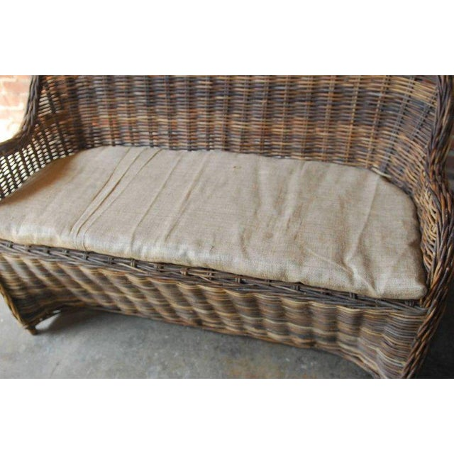 Distinctive organic modern woven rattan and wicker settee or dining bench seating. Constructed from a natural rattan frame...